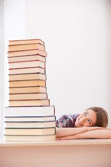 Sie liebt es zu studieren. fröhliches teenager-mädchen, das auf den großen stapel bücher schaut, die auf dem schreibtisch liegen