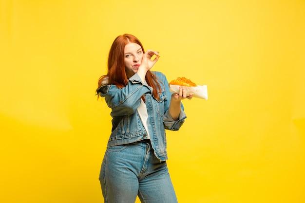 Sie müssen nicht mit essen fotografieren. kaukasische frau ist auf gelbem raum