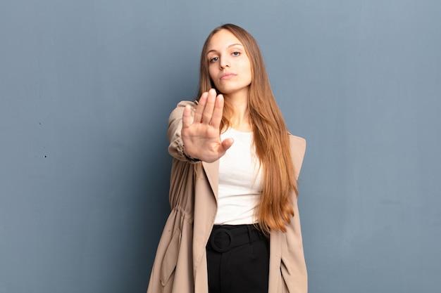 Sie sehen ernst, streng, unzufrieden und wütend aus und zeigen eine offene handfläche, die eine stoppgeste macht