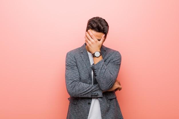 Sie sehen gestresst, beschämt oder verärgert aus, haben kopfschmerzen und bedecken das gesicht mit der hand