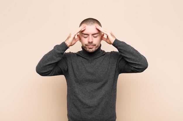 Sie sehen konzentriert, nachdenklich und inspiriert aus, machen ein brainstorming und stellen sich mit den händen auf der stirn vor