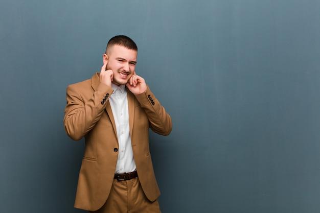 Sie sehen wütend, gestresst und genervt aus und bedecken beide ohren mit einem ohrenbetäubenden geräusch, geräusch oder lauter musik