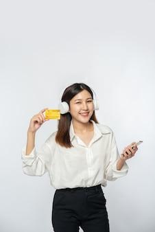 Sie trug ein weißes hemd und eine dunkle hose, um einkaufen zu gehen und eine kreditkarte und ein smartphone in der hand zu halten