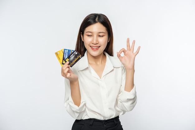 Sie trug ein weißes hemd und eine dunkle hose, um einkaufen zu gehen und eine kreditkarte zu halten