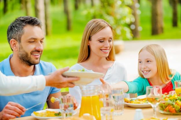 Sie will noch etwas salat. glückliche familie beim gemeinsamen essen am esstisch im freien