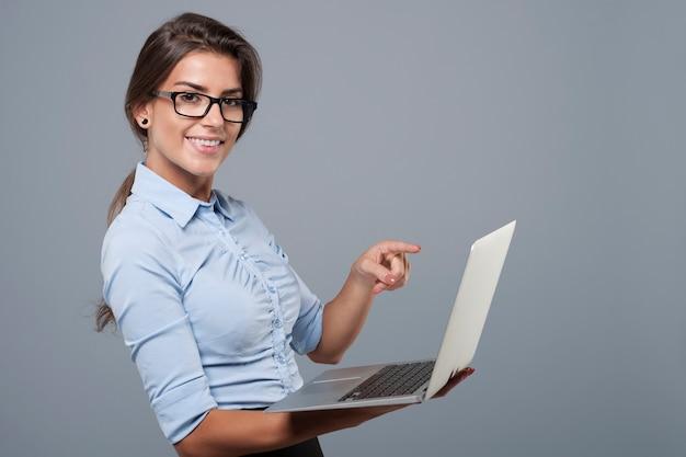 Sie zeigt auf einem modernen laptop