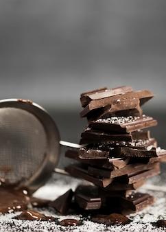 Sieb mit vorderansicht der geschmolzenen schokolade und des zuckers
