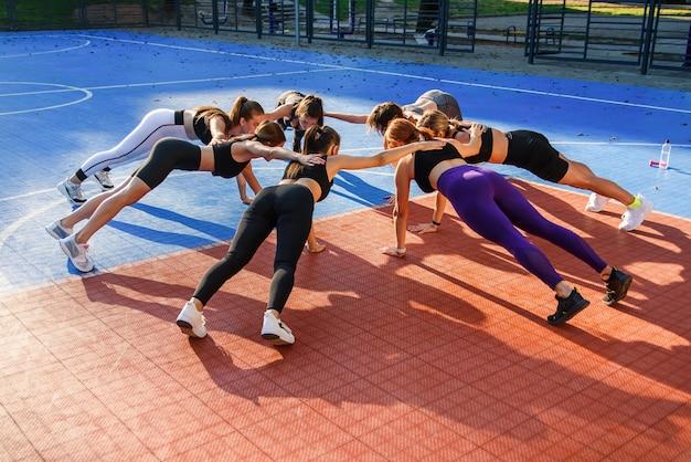 Sieben athletische frauen, die auf einer hand planken machen und sich im kreis auf dem freiluftstadion im modernen stadtpark gegenseitig auf den rücken legen.