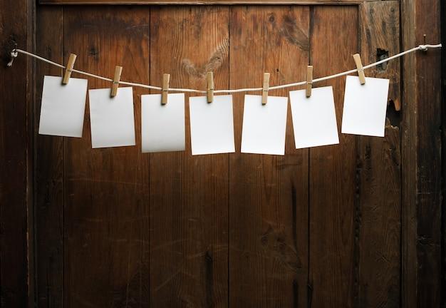 Sieben fotopapiere mit wäscheklammern auf holzuntergrund am seil befestigen