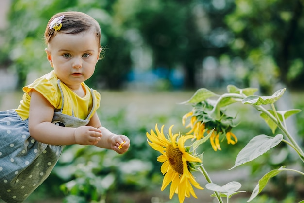 Sieben monate altes baby, das die sonnenblumenblätter hält und kamera betrachtet