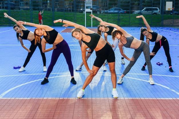 Sieben schlanke, sportliche junge frauen, die beim training im freien im stadtpark den körper nach links und rechts neigen.
