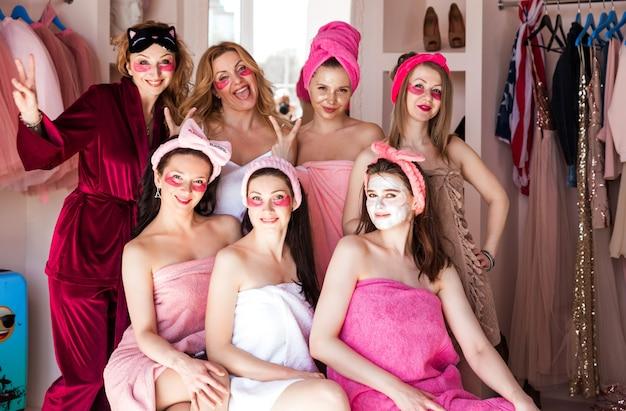 Sieben schöne junge frauen in rosa handtüchern mit kosmetischen bandagen auf dem kopf