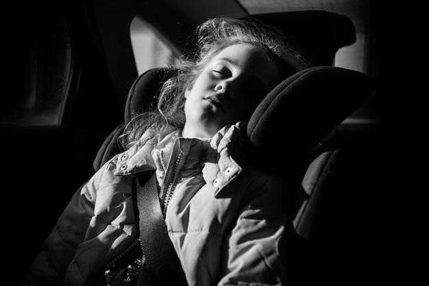 Siebenjähriges charmantes mädchen, das in einem kinderautositz schläft.