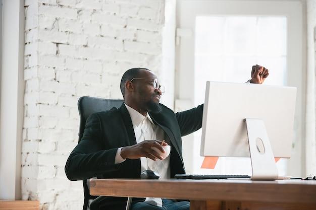 Sieg feiern. afroamerikanischer unternehmer, geschäftsmann, der im büro konzentriert arbeitet. sieht glücklich aus, fröhlich, trägt klassischen anzug, jacke. konzept der arbeit, finanzen, geschäft, erfolgsführerschaft