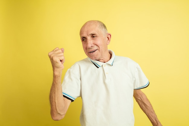 Sieg feiern. porträt des kaukasischen älteren mannes lokalisiert auf gelbem studiohintergrund. schönes männliches emotionales modell. konzept der menschlichen emotionen, gesichtsausdruck, verkauf, wohlbefinden, anzeige. copyspace.