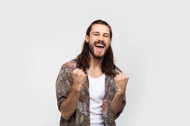 Sieg und feier geste, freude und freude .. hipster reisender stilvollen sorglosen mann auf einem weißen studio hintergrund, menschen lebensstil