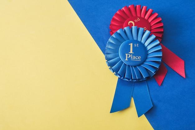 Sieger- und meisterauszeichnung für erfolg und zielerreichung. zwei rosetten 1. und 2. platz.