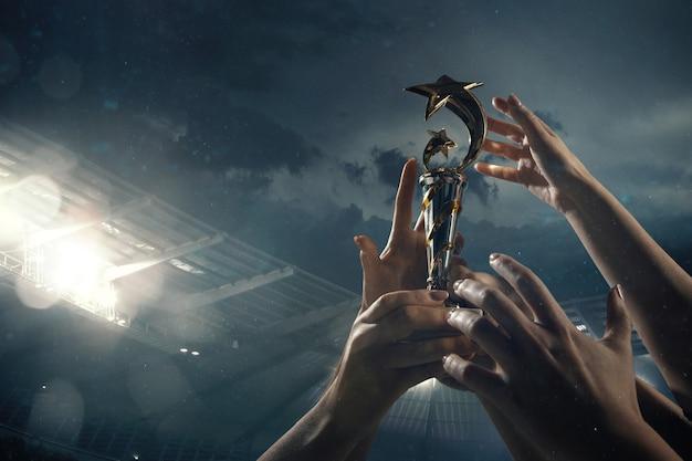 Siegespreis, männliche hände, die den siegerpokal gegen bewölkten dunklen himmel festziehen