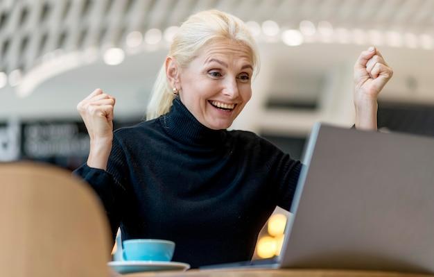 Siegreiche ältere geschäftsfrau, die über arbeit beim betrachten des laptops glücklich ist