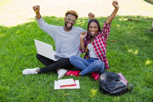 Siegreiche studenten posieren auf wiese
