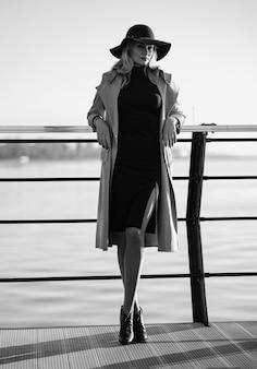 Sieh in jedem alter fantastisch aus. eine 40-jährige frau in einem mantel geht am damm entlang.