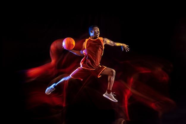 Siehe das ziel. afroamerikanischer junger basketballspieler des roten teams in aktion und neonlichtern über dunklem studiohintergrund. konzept von sport, bewegung, energie und dynamischem, gesundem lebensstil.