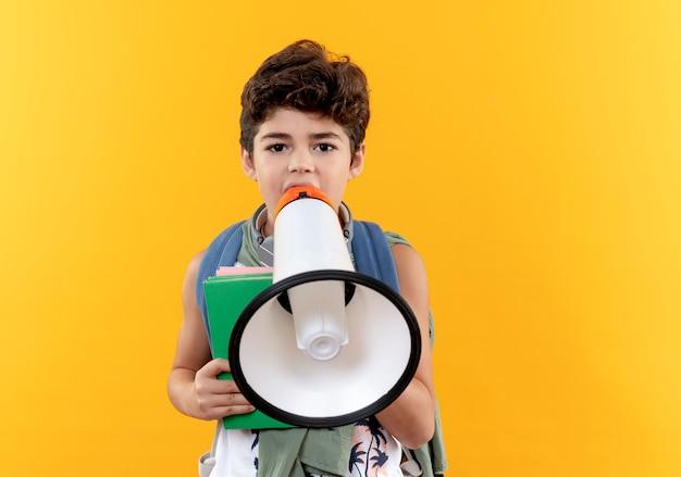Sieht ein kleiner schuljunge mit rucksack und kopfhörern aus, der ein buch hält und über lautsprecher spricht
