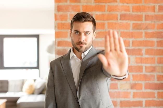 Sieht ernst, streng, unzufrieden und wütend aus und zeigt eine offene handfläche, die eine stopp-geste macht
