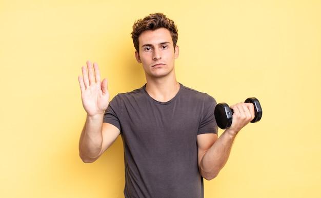Sieht ernst, streng, unzufrieden und wütend aus und zeigt eine offene handfläche, die eine stoppgeste macht. hantelkonzept