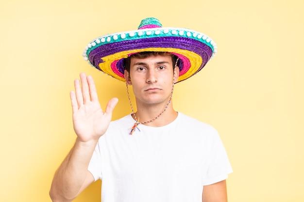 Sieht ernst, streng, unzufrieden und wütend aus und zeigt eine offene handfläche, die eine stoppgeste macht. mexikanisches hutkonzept