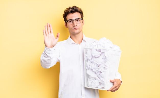 Sieht ernst, streng, unzufrieden und wütend aus und zeigt eine offene handfläche, die eine stoppgeste macht. papierkorbkonzept