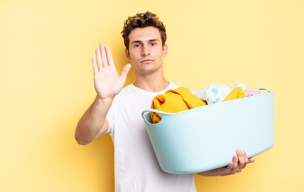 Sieht ernst, streng, unzufrieden und wütend aus und zeigt eine offene handfläche, die eine stoppgeste macht. waschen von kleidung konzept