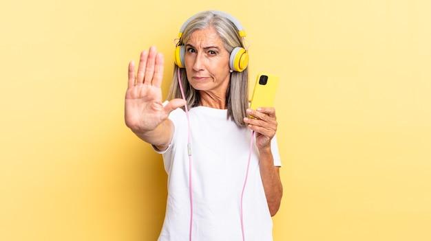 Sieht ernst, streng, unzufrieden und wütend aus und zeigt eine offene handfläche, die mit kopfhörern eine stopp-geste macht
