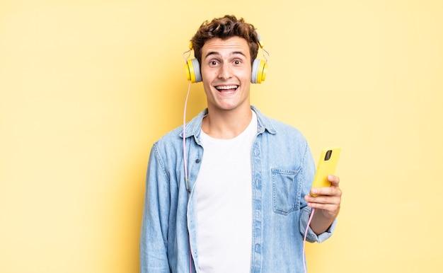 Sieht glücklich und angenehm überrascht aus, aufgeregt mit einem faszinierten und schockierten ausdruck. kopfhörer- und smartphone-konzept