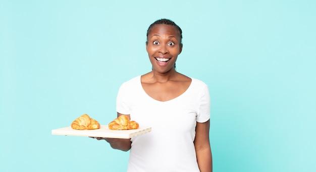 Sieht glücklich und angenehm überrascht aus und hält ein croissant-tablett in der hand