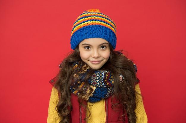 Sieht im winter süß aus. roter hintergrund des kleinen mädchens. kleines kind im wintermodestil. wintergarderobe für aktives kind. stil und mode. im winter warm halten.