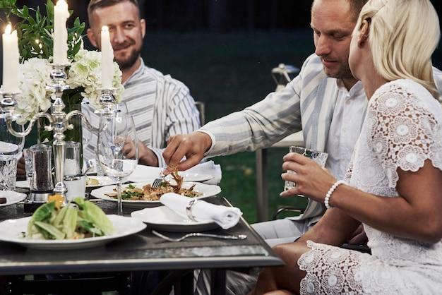 Sieht lecker aus. eine gruppe erwachsener freunde ruht sich abends im hinterhof des restaurants aus und unterhält sich.