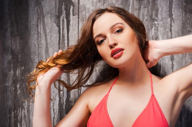 Sieht perfekt aus. schöne junge frau mit braunen haaren im roten bikini, die ihr haar berührt und die kamera anschaut, während sie gegen eine graue wand steht