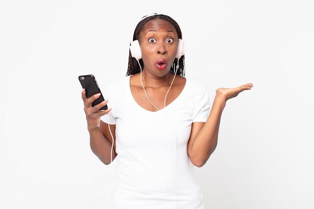 Sieht überrascht und schockiert aus, mit heruntergefallenem kiefer, der einen gegenstand mit kopfhörern und einem smartphone hält
