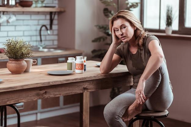 Sieht ungesund aus. depressive und gestresste reife frau, die ungesund aussieht, nachdem sie zu viele pillen eingenommen hat