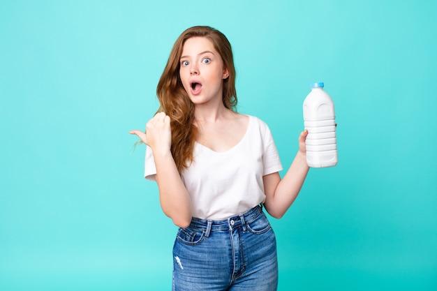 Sieht ungläubig aus und hält eine milchflasche in der hand