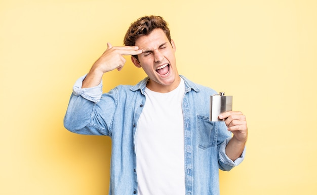 Sieht unglücklich und gestresst aus, selbstmordgeste, die waffenzeichen mit der hand macht und auf den kopf zeigt. konzept der alkoholflasche