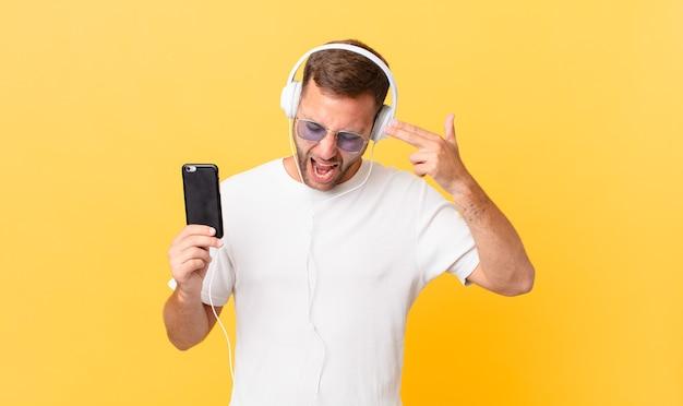 Sieht unglücklich und gestresst aus, selbstmordgeste macht waffenzeichen, hört musik mit kopfhörern und einem smartphone