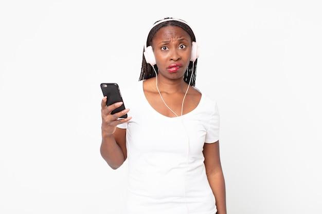 Sieht verwirrt und verwirrt aus mit kopfhörern und einem smartphone