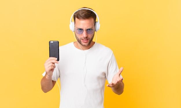 Sieht wütend, genervt und frustriert aus, hört musik mit kopfhörern und einem smartphone