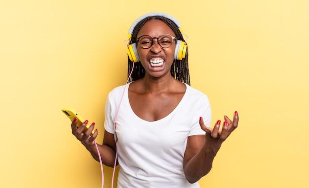 Sieht wütend, genervt und frustriert aus, schreit wtf oder was stimmt nicht mit dir und höre musik
