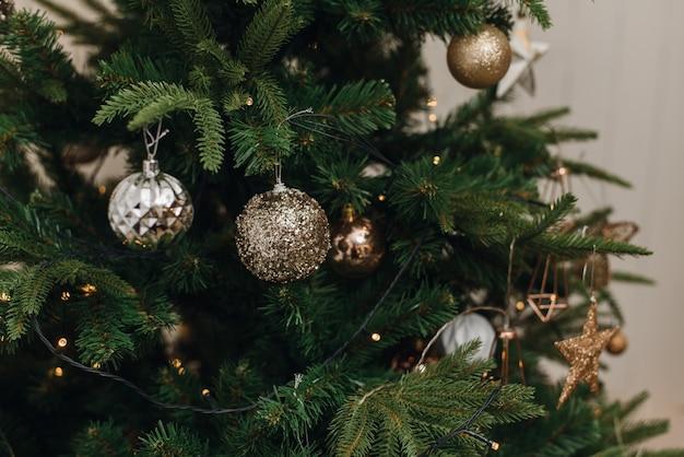 Silber, braunes gold verziert bälle auf weihnachtskunstbaum im haus