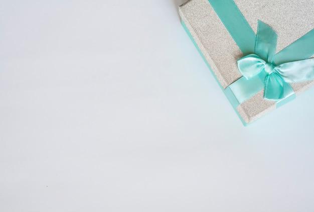 Silber geschenkbox mit blauer schleife auf weißem hintergrund, flache lage, kopienraum