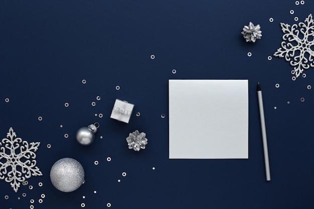 Silber leere weihnachtskarte und neujahrsdekorationen auf marineblau