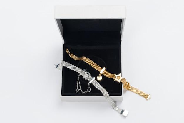 Silber- und goldarmbänder in geschenkbox, schmuck flach auf neutral gelegt. draufsicht auf mode-luxus-frauenaccessoires, schmuck und einkaufskonzept. trendy flat lay komposition.